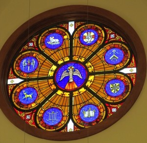 The East Window highlights the Holy Spirit and is surrounded with the symbols of The Hand of God, St. Joseph, The Dominican Shield, St. Thomas Aquinas, St. Lawrence, St. Dominic, The Blessed Virgin Mary, and Jesus, the Lamb of God.