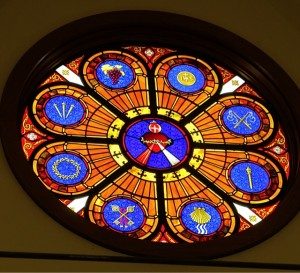 The West Window highlights the Sacred Heart of Jesus, surrounded by The Eucharist, Flagrum, Spear, Baptism, Reconciliation, Crown of Thorns, Three Nails, and Grapes & Vine.