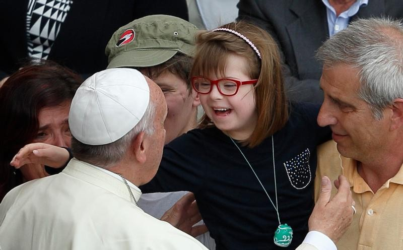 Pope Francis greets a girl after celebrating a Mass for the sick and disabled in St Peter's Square at the Vatican on June 12 (CNS)