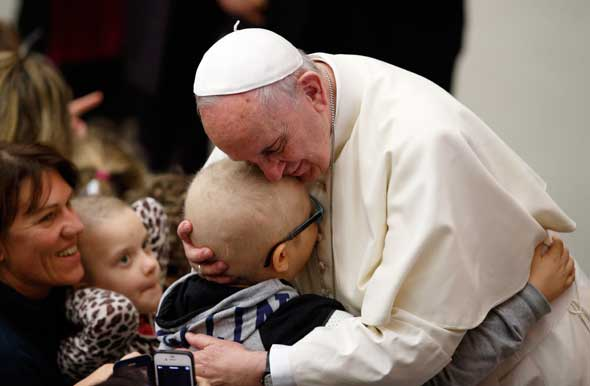 Pope Francis embraces a child as he meets the disabled during his general audience in Paul VI hall at the Vatican