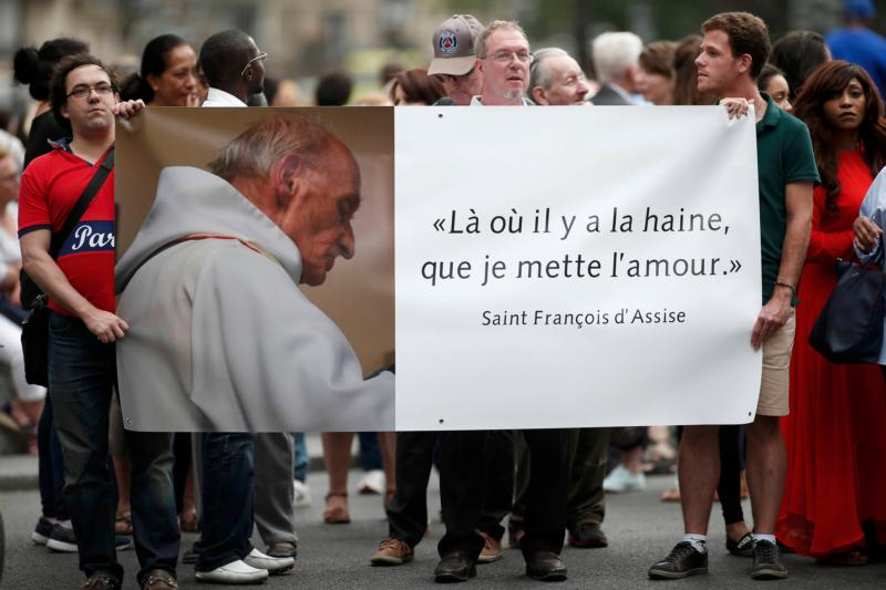 "People hold a banner with a picture of French priest Father Jacques Hamel, which reads, ""Where there is hatred, let me sow love,"" after a July 27 Mass at the Notre Dame Cathedral in Paris. (CNS photo/Benoit Tessier, Reuters)"