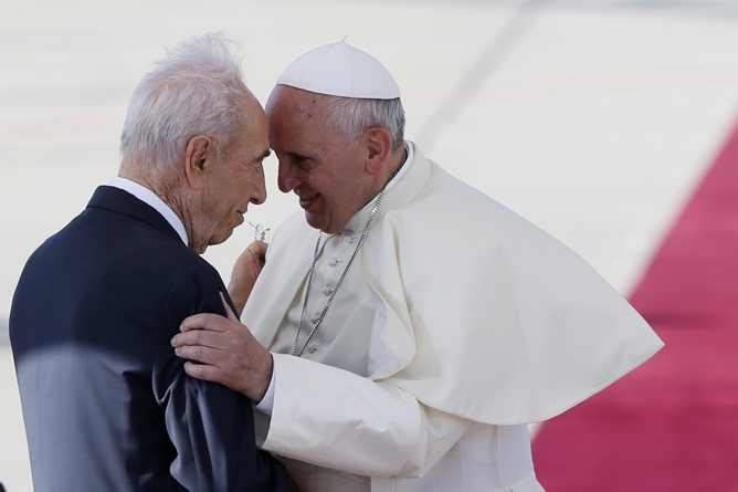 Israel's President Shimon Peres (L) seen embracing Pope Francis (C) on the red carpet at a welcoming ceremony, as the pope lands at Ben Gurion international airport, near Tel Aviv. Pope Francis arrived in Israel today, May 25, 2014, for his first official visit in the region. I hope that the memory of Shimon Peres and his many years of service will inspire us all to work with ever greater urgency for peace and reconciliation between peoples. (Pope Francis on Instagram)